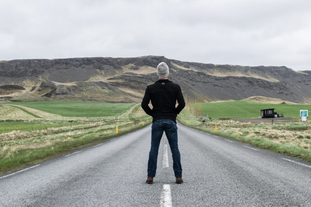 A man is standing on an empty road with countryside around and hills ahead. He is lost.