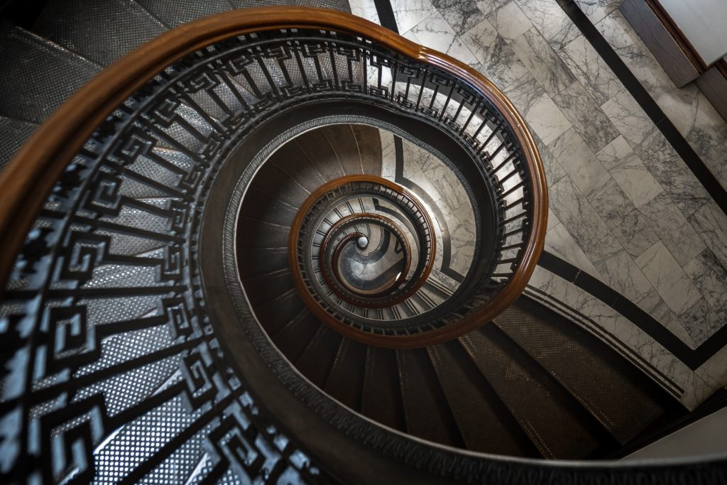 A spiral staircase, photographed from the top. It is a confusing image to understand what is going on, as the concentric circle gets smaller and smaller as it goes down.
