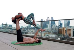 Shows 2 people staying in balance, in a yoga position. It takes both to create this.