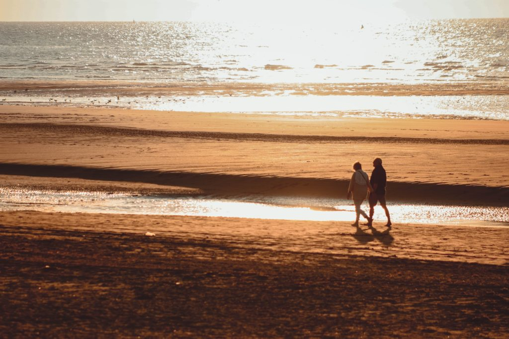 2 people walking along a beach, on orange coloured sad, at sunset