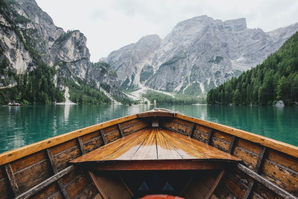 sitting in a wooden rowing boat, looking out over the front, at a green body of water and rocky mountains ahead. A sense of adventure or exploration.